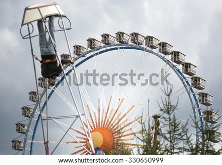 MUNICH, GERMANY - SEPT 28:  Oktoberfest 2015, giant wheel with swing boat in foreground - stock photo