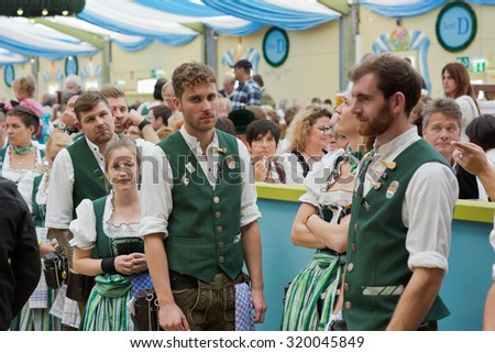 MUNICH, GERMANY - SEPT. 19, 2015: Staff in the Spatenbrau Tent with Traditional Costumes Serve Visitors at the Oktoberfest. The Festival runs from Sept. 19th until Oct. 4th 2015 in Munich, Germany. - stock photo