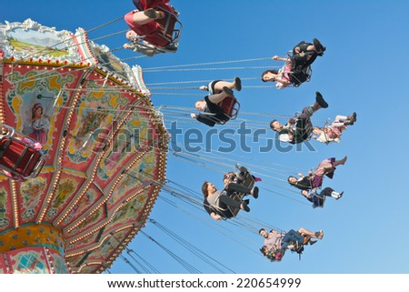 MUNICH, GERMANY - SEPT. 27, 2014: Visitors on an Old Fashion Carousel at the 181st Oktoberfest. The Festival runs from Sept. 20 - Oct. 5  in Munich, Germany - stock photo