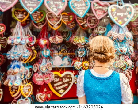 MUNICH/GERMANY - SEPTEMBER 2017: a young woman dressed for the beer festival looking to the typical Oktoberfest sweets