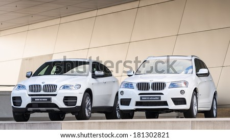 MUNICH, GERMANY - SEPTEMBER 28, 2012: New models of X3 X6 SUV against modern design building. Two white cars on podium wet after rain. - stock photo