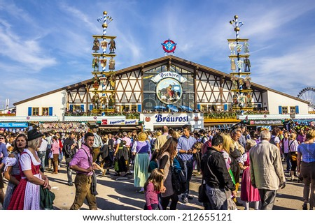 MUNICH, GERMANY - SEPTEMBER 23, 2012: Oktoberfest, Munich: One of the big beer tents. In the foreground, people are walking along, partly dressed in traditional costumes. - stock photo