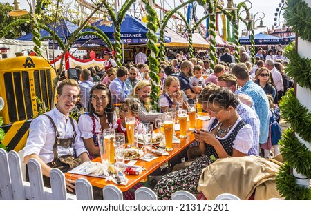 MUNICH, GERMANY - SEPTEMBER 23, 2012: Oktoberfest munich: People dressed in traditional costumes are sitting in the beergarden. - stock photo