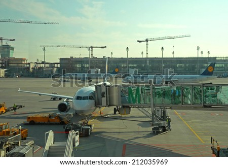 MUNICH, GERMANY-SEPTEMBER 25, 2013: passengers airplane decking. With 38 millions passengers per year it is one of the most important airport in Europe.