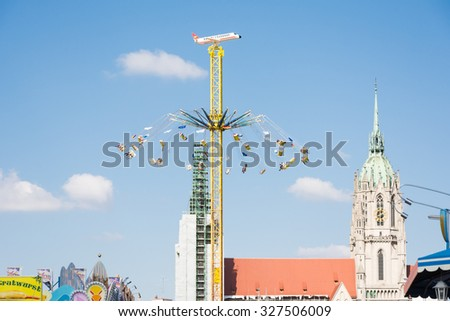 MUNICH, GERMANY - SEPTEMBER 30: People in a chairoplane on Oktoberfest in Munich, Germany on September 30, 2015. Oktoberfest is the biggest beer festival of the world with over 6 million visitors. - stock photo