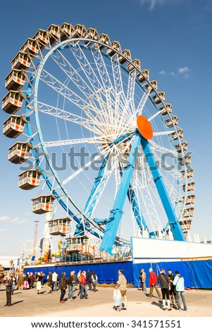 MUNICH, GERMANY - SEPTEMBER 30: People in front of a ferris wheel on the Oktoberfest in Munich, Germany on September 30, 2015. The Oktoberfest is the biggest beer festival of the world. - stock photo