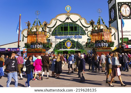 MUNICH, GERMANY - SEPTEMBER 23, 2014: The Oktoberfest in Munich is the biggest beer festival of the world. The visitors are walking at the mainstreet with tents of bavarian breweries. - stock photo