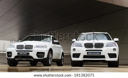 MUNICH, GERMANY - SEPTEMBER 19, 2012: Two new white BMW X3 and X6 SUV against modern design building. Wet cars on podium after rain. - stock photo