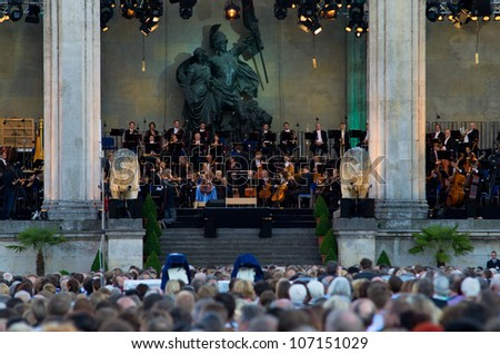 MUNICH - JULY 7: Juraj Valcuha, Conductor, and Sol Gabetta, Violoncello, with the Munich philharmonic orchestra at the open-air classic festival classic at the Odeonsplatz in Munich on July 7, 2012. - stock photo
