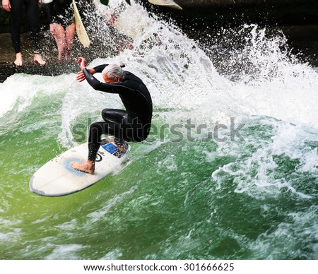 MUNICH - JULY 12: surfer in English Garden on July 12, 2015 in Munich, Germany. The river Isar in Munich is a lovely place of Munich's surfers.  - stock photo