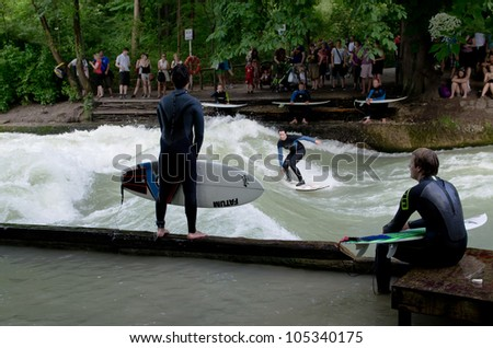 MUNICH - JUNE 16: The Eisbach (German for ice brook), located in the park Englischer Garten, forms a standing wave, which is a popular river surfing spot in Munich, Germany on June 16, 2012.