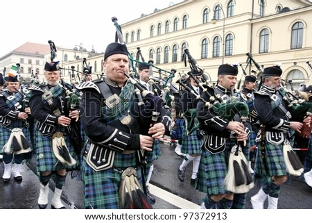 MUNICH - MARCH 11: irish bagpipers march at St. Patrick's day on March 11, 2011 in Munich, Germany. This national Irish holiday takes place annually in March in Dublin and other European cities. - stock photo