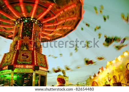 MUNICH - OCT 4: A spinning illuminated chairoplane on the Oktoberfest fairground at night on October 4, 2010 in Munich, Germany. - stock photo