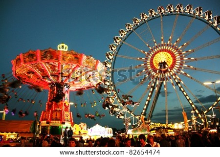 MUNICH - OCTOBER 4: An illuminated chairoplane and a big wheel on the Oktoberfest fairground at night on October 4, 2010 in Munich, Germany. - stock photo