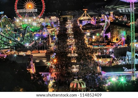 MUNICH - SEPTEMBER 28: Large numbers of tourists and locals come to see the attractions of the world's famous fun fair and beer festival Oktoberfest in Munich, Germany at night on September 28, 2012.