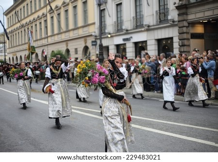MUNICH - SEPTEMBER 21:performer are marching  at the opening of Oktoberfest (Trachtenzug)  on September 21, 2014 in Munich, Germany. This famous Bavarian beer festival takes place annually in Munich. - stock photo