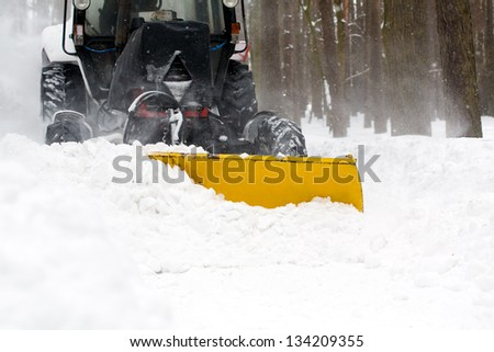 Municipal equipment removing snow from the roads in winter - stock photo