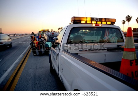 Municipal roadside assistance helping to tow away a broken car off the freeway at sunset - stock photo