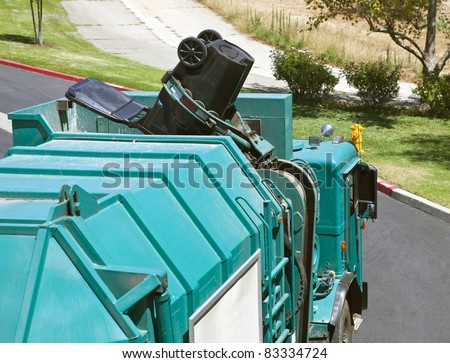 Municipal robotic arm trash truck dumps a large black can. - stock photo