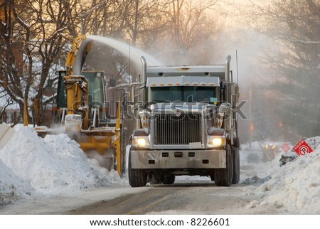 Municipal snow removal crew at work; snow thrower and dump truck on street of snow - stock photo