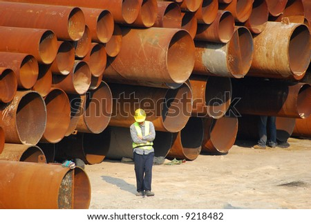 Municipal water pipes and a worker with a hard hat - stock photo
