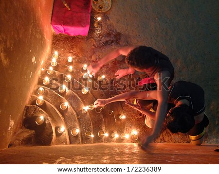 MUNNAR, INDIA - JANUARY 2: Men lighting prayer candles before performing in a fire show in Thirumeny cultural centre on January 2, 2014 in Munnar, Kerala, India. - stock photo