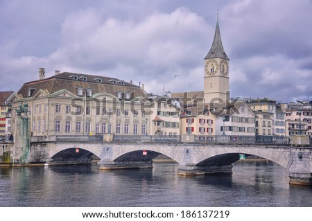 Munster bridge over Limmat river in Zurich, Switzerland. St. Peter Church old Clock tower is one of the symbols of the city and major touristic attraction - stock photo