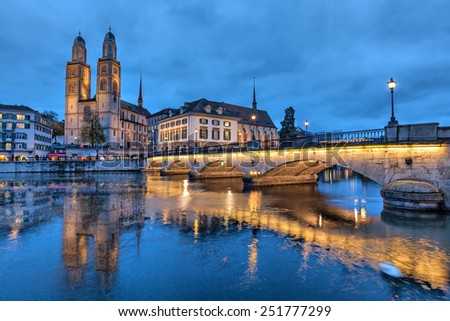 Munsterbrucke and Grossmunster church reflecting in river Limmat, Zurich, Switzerland - stock photo