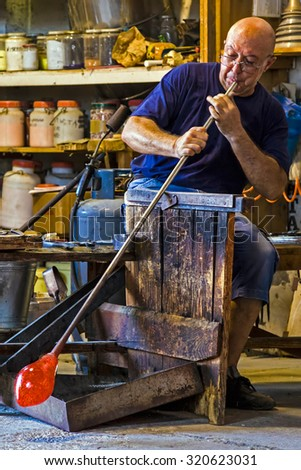 MURANO, ITALY - AUGUST, 5: Glass worker in action in the Murano glass factory on August 5, 2015. - stock photo