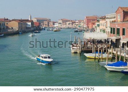 MURANO, ITALY - FEBRUARY 27, 2007: View to the Grand canal, boats, buildings and people at the street in early spring in Murano, Italy. - stock photo