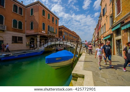 MURANO, ITALY - JUNE 16, 2015: Murano stone bridge in the middle of canals, blue transportation boat and turists.