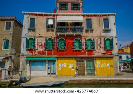 MURANO, ITALY - JUNE 16, 2015: Nice colorfull house in Murano, traditional architecure with various colors, boat outside.  - stock photo