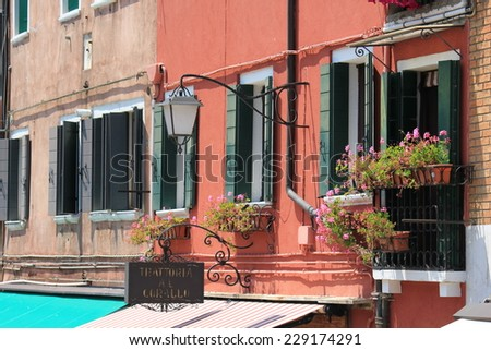 Murano, Italy, June 6 2014: Tyical view of the little island of Murano, near Venice, famous for its colored house and canals. House architectural detail with its shutters - stock photo