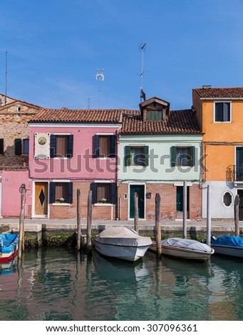 MURANO, ITALY - 14TH MARCH 2015: A view of buildings and boats in Murano along the waterfront during the day. - stock photo