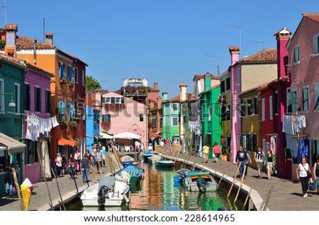 MURANO - SEP 23, 2014: Tourists from all the World are walking along water canal famous Burano island, Venice. Landmark of Veneto region, Italy - stock photo