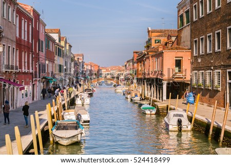 Murano Venice, Italy - October 29, 2016: View of the central canal on Murano island in Venice Italy. The canal is surrounded with tourist shops selling the famous Murano glass