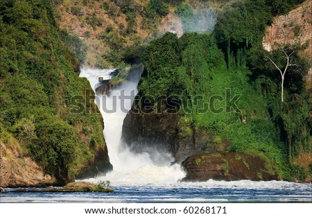 Murchison  falls. Murchison  falls roar, clamped between two rocks covered with greens. - stock photo