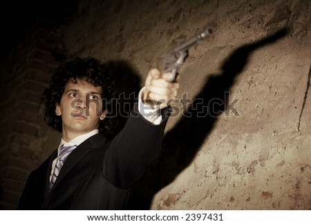 Murder in action: the gangster is gonna push the trigger! - stock photo