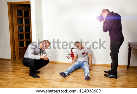 Murder scene with two forensic analysts investigating a crime - stock photo