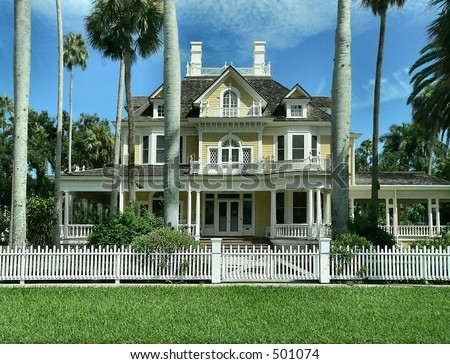 Murphry-Burroughs House, a turn of the century American home built in the Georgian Revival style in Ft. Myers, Florida.  The house is pale yellow with white trim and has a white picket fence.