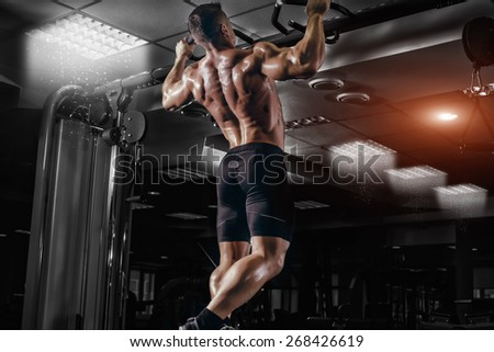 Muscle athlete man in gym making elevations. Bodybuilder training in gym - stock photo