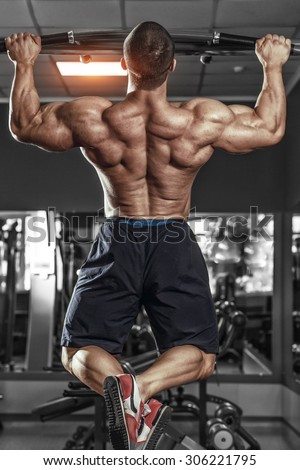 Muscle athlete man in gym making Pull-up. Bodybuilder training in gym - stock photo