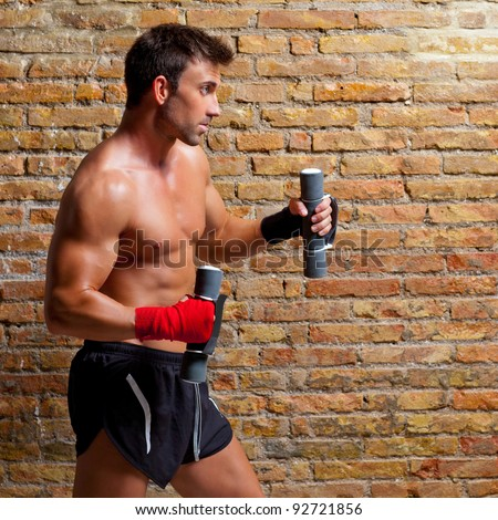 muscle boxer man with fist bandage and training weights