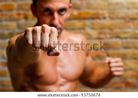 muscle boxer shaped man fist to camera on brick wall