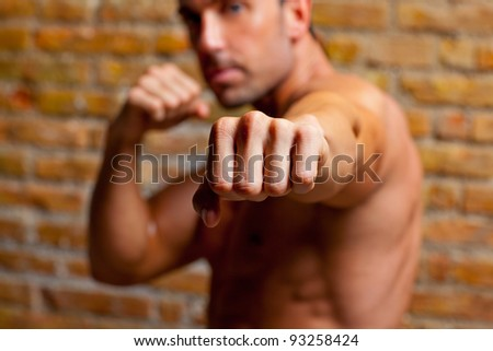 muscle boxer shaped man fist to camera on brickwall - stock photo