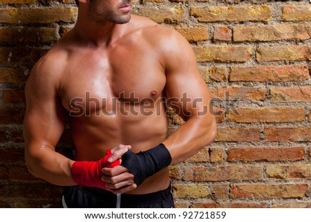muscle boxer shaped man with fist bandage in red and black - stock photo