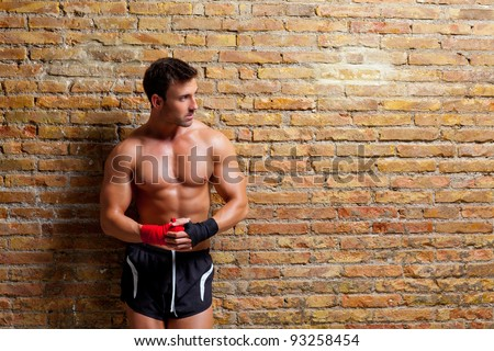 muscle boxer shaped man with fist bandage in red and black on brick wall - stock photo