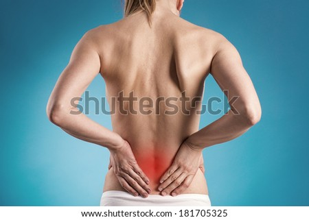 Muscle cramp or backache on naked woman's back. Young female touching her painful back.  - stock photo