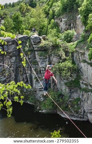 Muscle guy in red shirt walking on tightrope above the river - stock photo