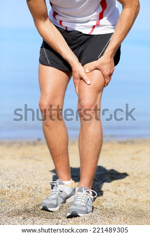 Muscle injury. Man runner with sprain thigh muscles. Athlete running in sports shorts clutching his thigh muscles after pulling or straining them while jogging on the beach. - stock photo